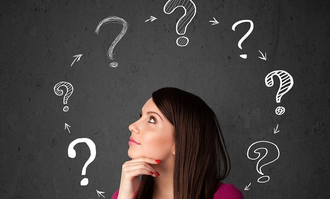 Young woman thinking with question mark circulation around her h